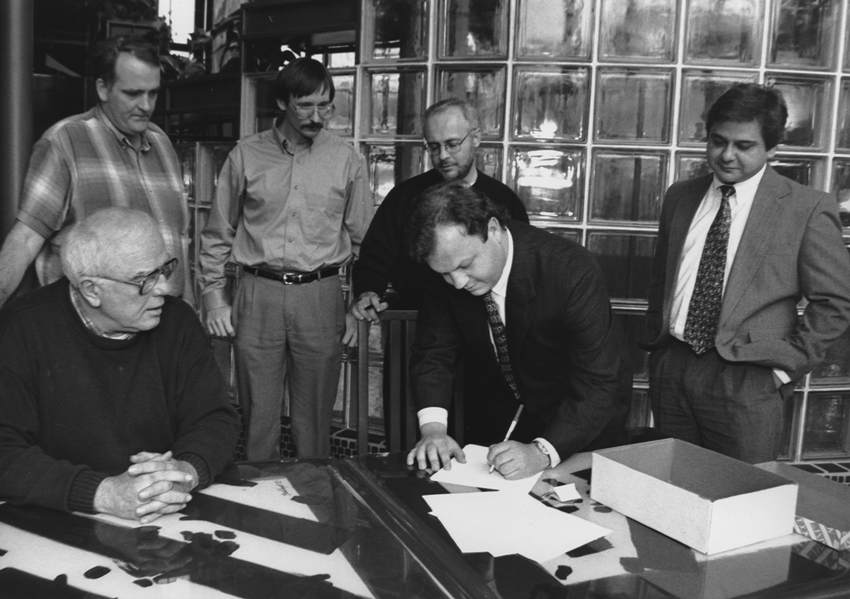 During a January 5, 1996, meeting in Nashville, Tennessee, Perry Stambaugh, editor of Penn Lines magazine, signs papers formally incorporating National Country Market Sales Cooperative (NCM). Looking on, from left, are fellow NCM incorporators Bill Roberts, editor of Oklahoma Living; John Bruce, associate editor with Cooperative (then Rural) Living (VA); Jim McCarty, editor, Rural Missouri; Rod Guge, editor, The Tennessee Magazine; and George Macias, editor, Texas Co-op Power and NCM's first executive director.